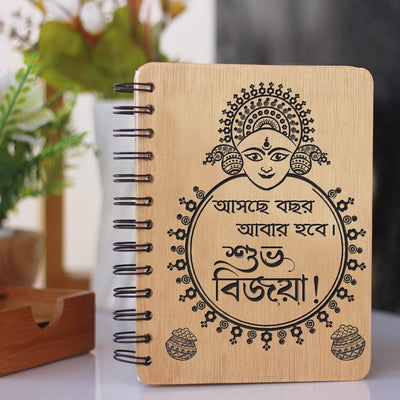 Asche Bochor Abar Hobe. Subho Bijoya! A Personalized Notebook Wishing Loved Ones Shubho Bijoya. Dashami Wishes Engraved In Bengali On Wooden Notebook. Looking for durga puja gift ideas? This wooden diary is the best durga puja gift.
