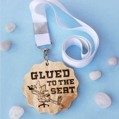 Glued To The Seat Funny Medal. This wooden medal is the best gift for coworkers. This custom medal will make great office gifts. Buy more customised gifts for colleagues from The Woodgeek Store.