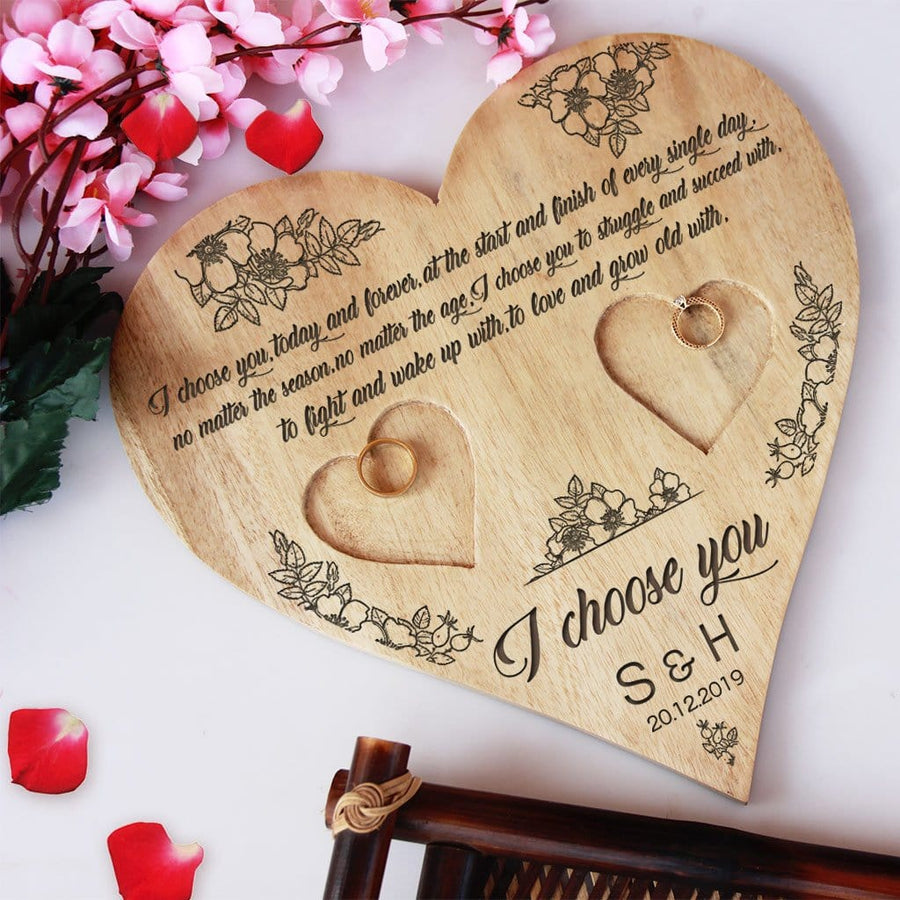 A Wooden Heart Ring Holder Engraved With A Love Quote: I choose you, today and forever, at the start and finish of every single day, no matter the season, no matter the age, I choose you to struggle and succeed with, to fight and wake up with, to love and grow old with. I choose you. This Personalised Ring Tray Is Engraved With Initials & Date. This engagement ring tray is one of the best engagement gifts for couples and wedding gifts.