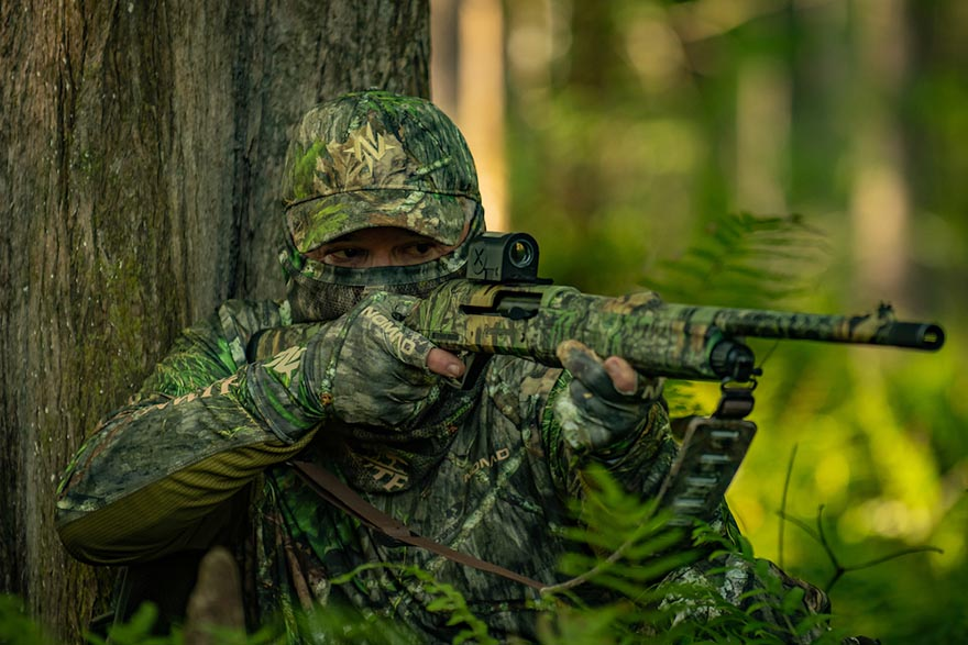 camouflaged man aiming gun