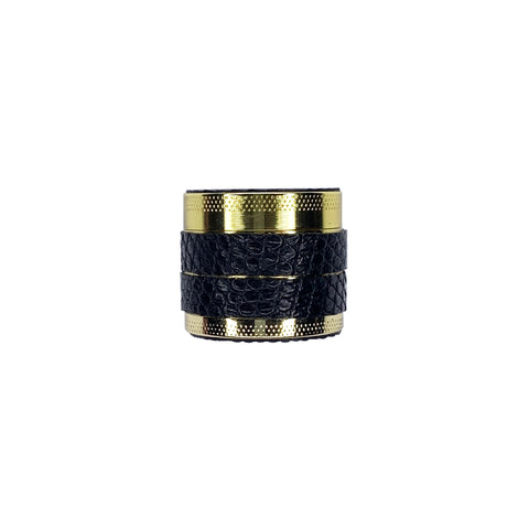 Gold multi chamber herb grinder wrapped in black lizard.