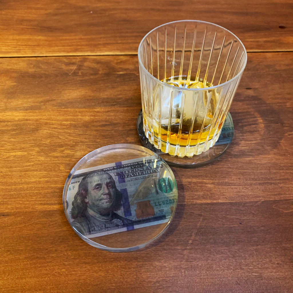 Still life image of clear resin coaster with one hundred dollar bill inside