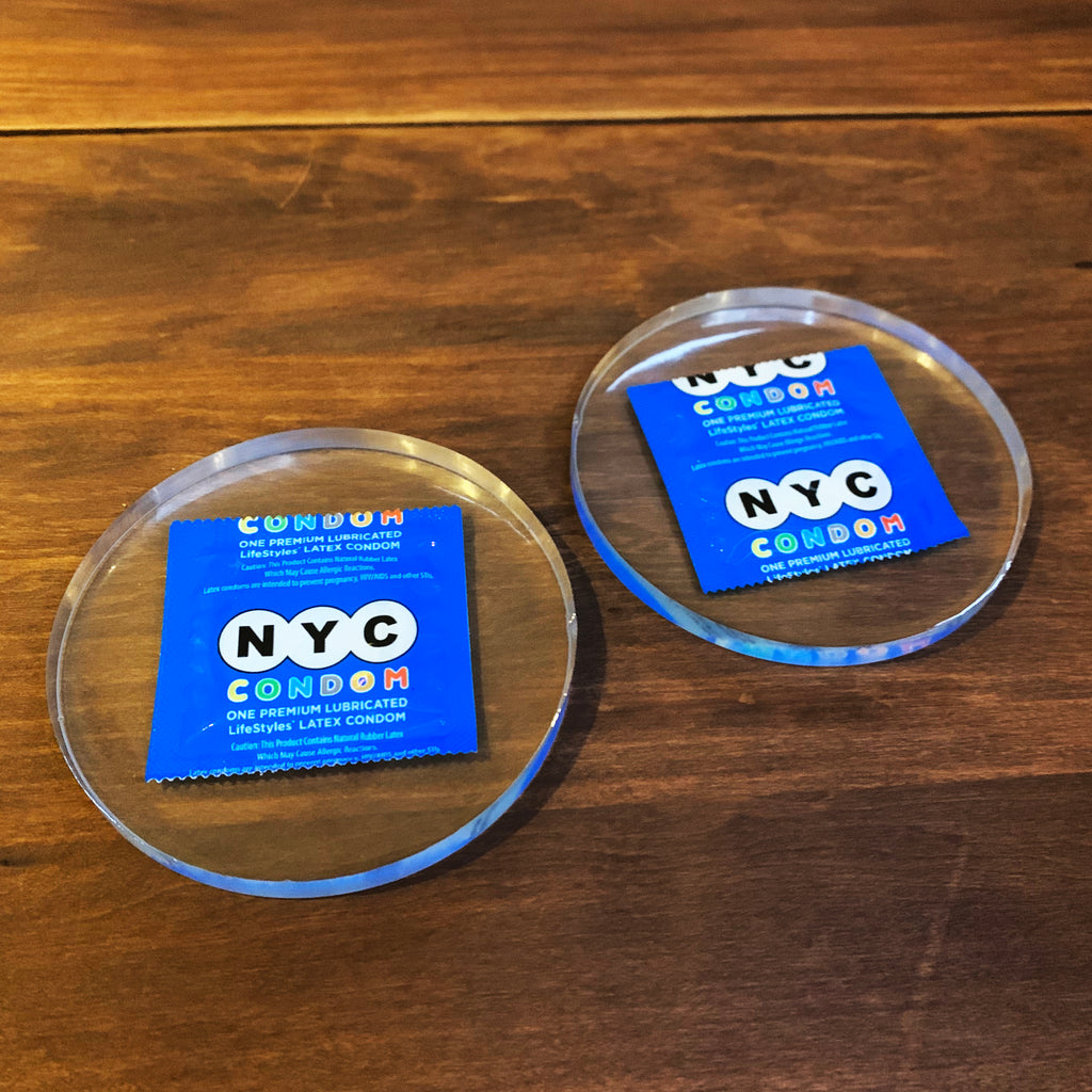 Clear resin drink coasters with blue NYC condoms encased inside