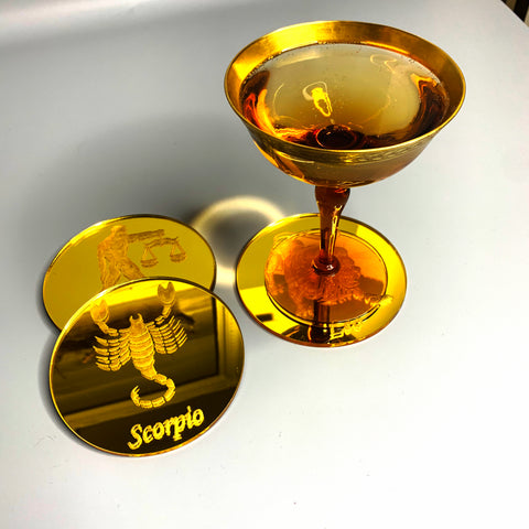 Round, gold mirrored acrylic drink coasters engraved with the scorpion zodiac sign