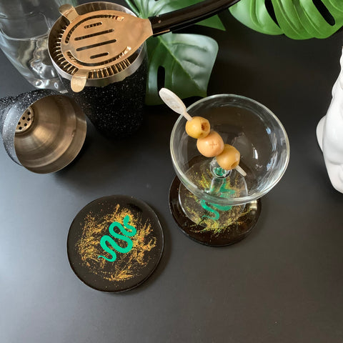 Black and gold glitter resin drink coasters with mirrored green serpent encased inside