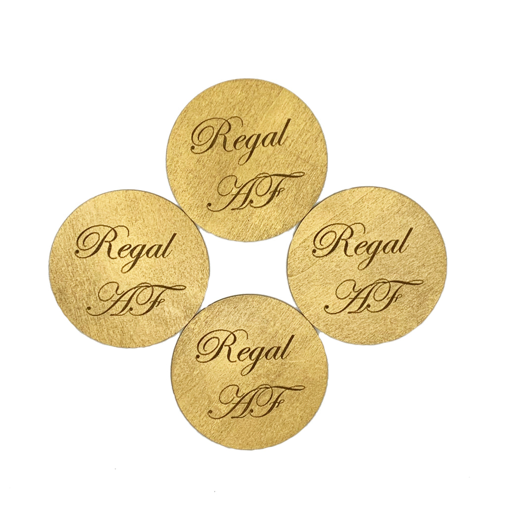Round wood drink coasters coated in metallic gold and engraved with Regal AF