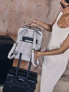 women is attaching beige stone CALPAK Kaya laptop backpack to carry on using a luggage sleeve