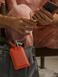 red luggage tag with portable chargers inside