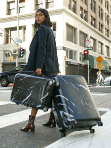 woman rolling large 29 inch black marble hardside suitcase from CALPAK Astyll luggage collection