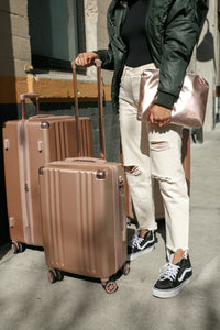 woman with rose gold CALPAK Ambeur hard shell rolling carry on