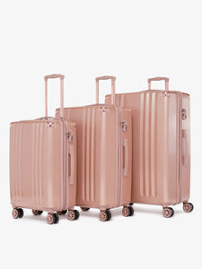 rose gold CALPAK Ambeur 22 inch hard shell carry on suitcase as a part of a luggage set