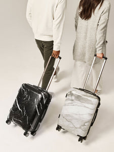 couple rolling CALPAK Astyll black and white hardside marble carry on suitcases