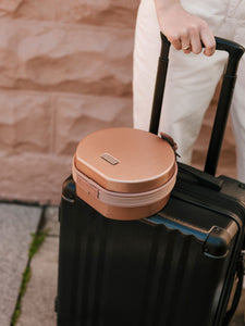 rose gold CALPAK Baye Mini makeup bag attached to CALPAK Ambeur carry on