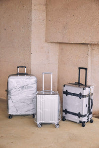 hardside carry on, medium suitcase and large luggage packed in clear plastic luggage cover