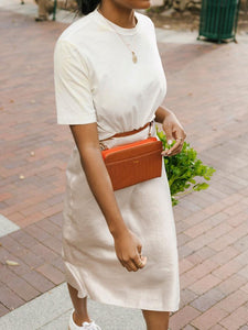 woman wearing CALPAK cognac brown faux crocodile leather travel wallet as a fanny pack