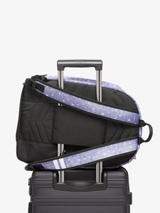 CALPAK denim Glenroe backpack attached to carry on suitcase
