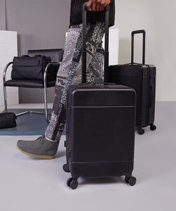 model rolling a black CALPAK Hue hard shell carry-on suitcase