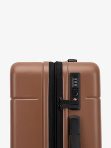 TSA lock of CALPAK Hue hard shell rolling carry-on luggage in brown hazel color