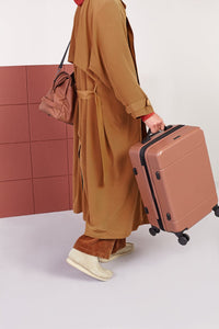 male model holding CALPAK Hue hard shell carry-on suitcase with spinner wheels in brown hazel color