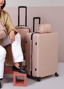 woman with large hardside polycarbonate suitcase in pink sand color from CALPAK Hue luggage collection