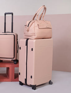 large hardside polycarbonate suitcase in pink sand color with duffel and carry on from CALPAK Hue luggage collection