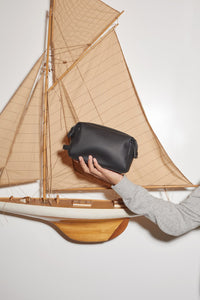 model holding CALPAK black toiletry bag from Hue collection