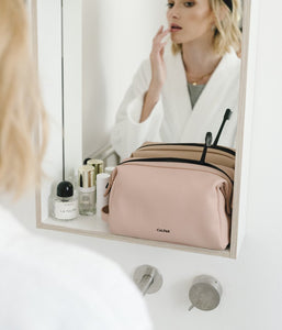CALPAK pink makeup bag from Hue collection on the bathroom shelf