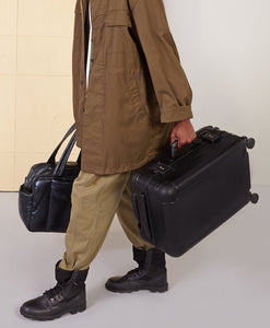 male model holding premium black CALPAK Jen Atkin hard shell carry-on luggage