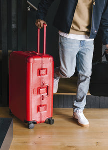 man rolling large red CALPAK Jen Atkin luggage