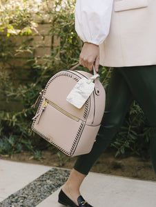 Pink blush CALPAK Kaya backpack with power luggage tag