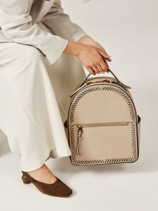 model holding beige stone CALPAK Kaya backpack