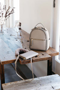 Beige CALPAK Kaya backpack with travel wallet on the table