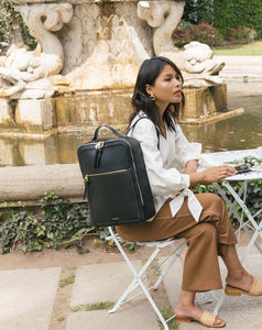 female model with black CALPAK Kaya laptop backpack