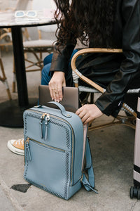 model with CALPAK Kaya laptop backpack in blue bell color