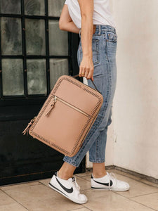 female model with a caramel brown CALPAK Kaya laptop backpack