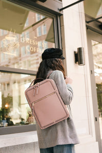 women with mauve pink CALPAK Kaya laptop backpack