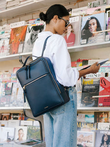female model wearing navy blue CALPAK Kaya laptop backpack