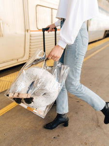model carries clear bag with white silk travel neck pillow and sleeping mask