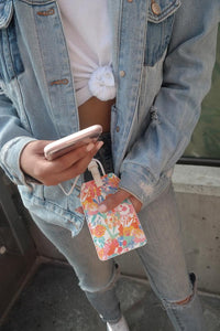 Model charging her phone with Oh Joy! power luggage tag in floral