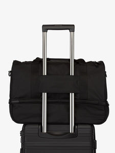 black CALPAK Stevyn duffel bag with luggage trolley sleeve