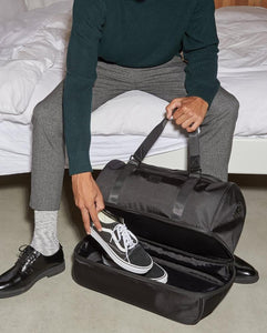shoe compartment in black CALPAK Stevyn duffel bag