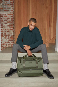 male model with green moss CALPAK Stevyn duffel bag