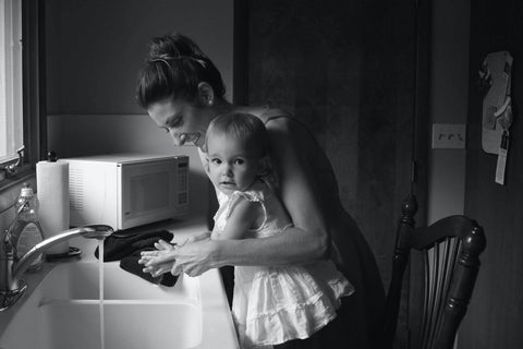 A parent helping their child, who is standing on a chair by the sink, wash their hands.