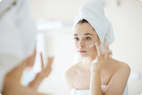 An individual wrapped in towels stands in front of a mirror, applying moisturizer to their face.