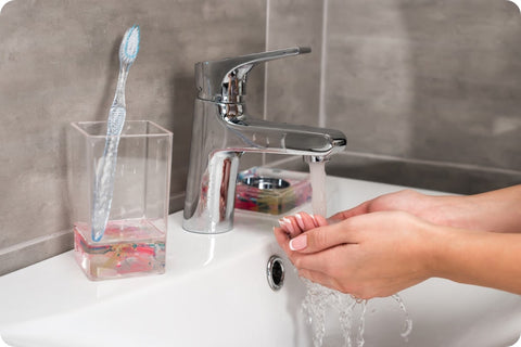 Close-up of a person washing their hands in a bathroom sink, a toothbrush resting in a drinking glass against the backsplash.