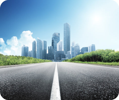 View of a city skyline against a blue sky, from the street level of an asphalt road outside the city.