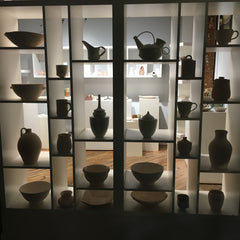 clay gallery with 24 vases on a shelf