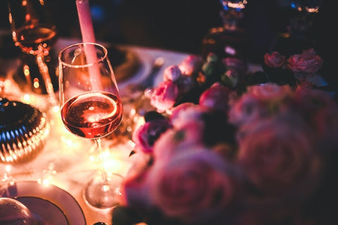 candlelit dinner table with flowers and wine