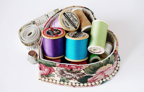 thread, bobbin, measuring tape, sewing kit