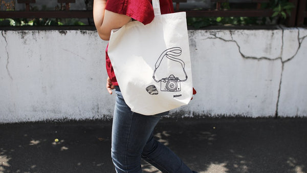 woman carrying canvas tote bag screen printed with camera